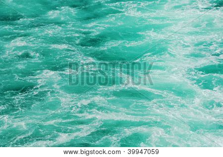 Turquoise sea with waves and foam