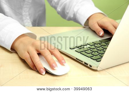 female hands writing on laptot, on green background