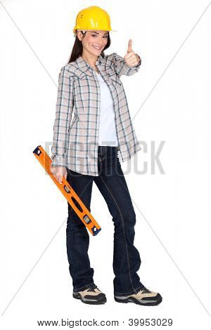 Woman holding spirit-level and giving the thumbs-up