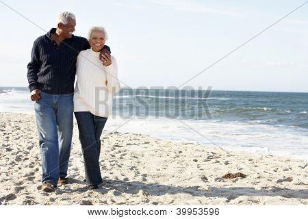 Senior Couple Walking Along Beach Together