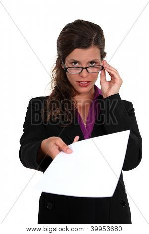 Businesswoman peering over her glasses and holding out a document
