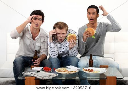 Three young eating burgers and drinking beer