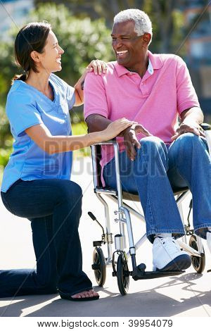 Carer Pushing Senior Man In Wheelchair