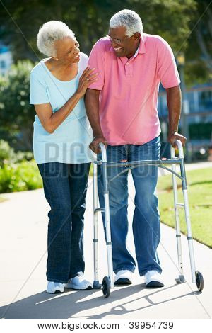 Senior Woman Helping Husband With Walking Frame