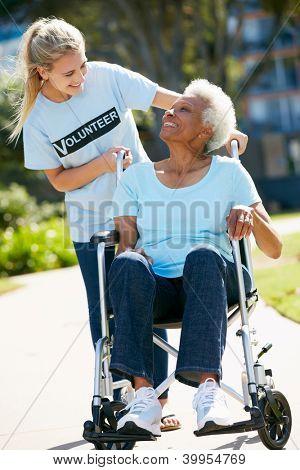 Teenage Volunteer Pushing Senior Woman In Wheelchair