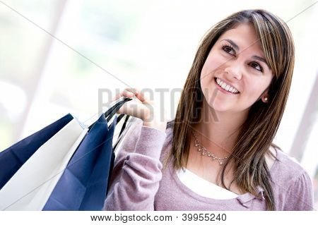 Pensive shopping woman looking up and holding bags
