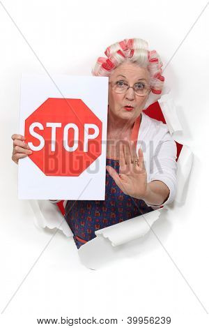 An old lady with a stop sign.