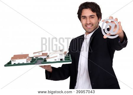 Architect with a model of a housing estate and an sign