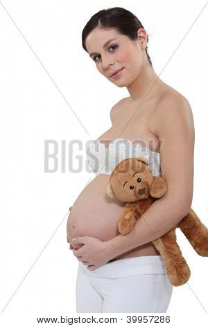 beautiful young pregnant woman with bare belly and teddybear