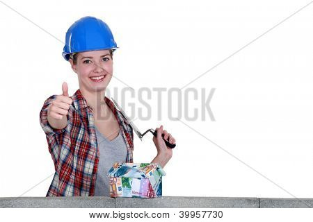 craftswoman looking at a house of bills and making a thumbs up sign
