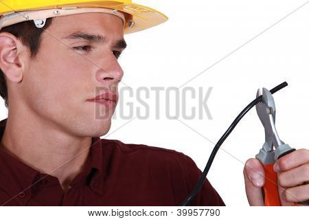 Man carefully cutting electrical wire