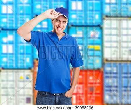 Portrait of a smiling worker in front of a stack of containers