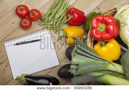 Book with pen and vegetables
