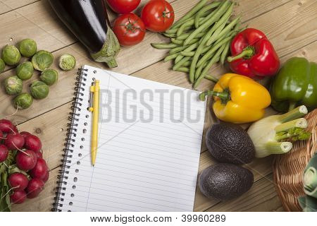 Vegetables with book and pen on wooden surface