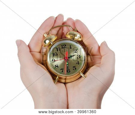 The alarm clock in female hands isolated
