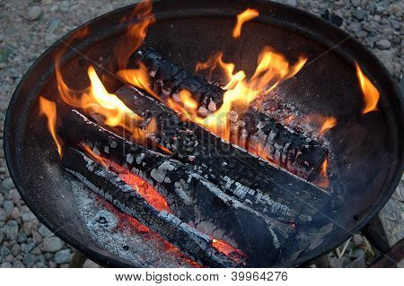 burning log in a round metal caldron