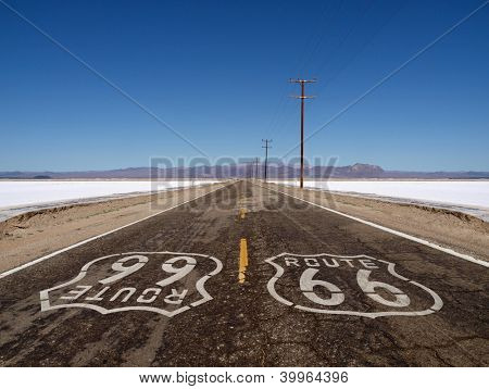 Route 66 sign painted on rough Mojave desert salt flat highway pavement.