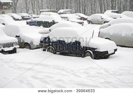 Carros estacionados, cobertos de neve
