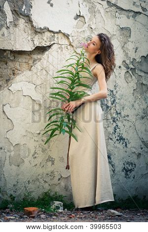 Beautiful Woman On Background Of Old Wall