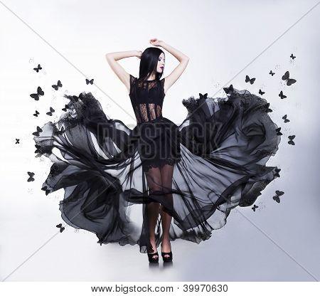 Swing. Sensual Woman In Black Fluttering Dress With Butterflies
