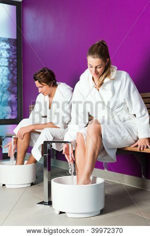 Couple - man and woman - having hydrotherapy water footbath in spa setting