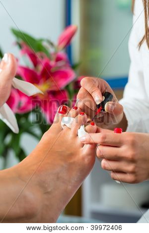 Woman receiving pedicure in a Day Spa, feet nails get polish