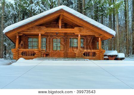 Holzhaus im verschneiten Wald