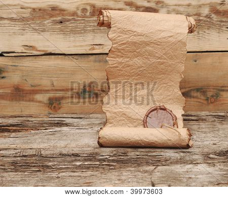 Ancient scroll with wax seal on wooden table
