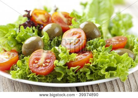 fresh salad with tomatos, olives, lettuce and cucumber