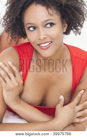 A beautiful sexy mixed race African American girl or young woman laying down wearing a red dress