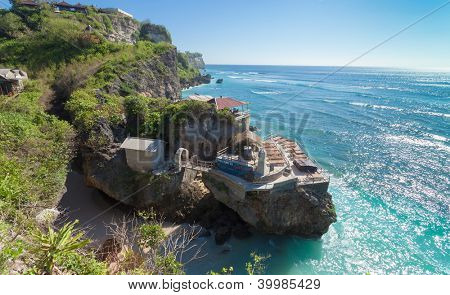 Ulu Watu coastline with beaautiful rocky cliffs and turquoise wavey sea.
