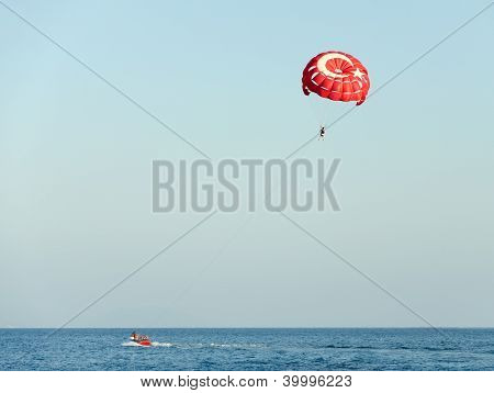 Parasailing on a red parachute
