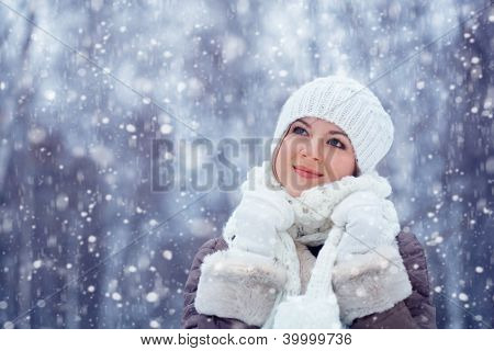 beautiful woman walking outdoors under snowfall