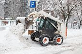 image of snow shovel  - small excavator bobcat working on the street cleaning snow - JPG