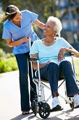 foto of wheelchair  - Carer Pushing Senior Woman In Wheelchair - JPG