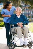 stock photo of wheelchair  - Carer Pushing Senior Man In Wheelchair - JPG