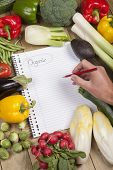image of brinjal  - Cropped image of hand writing list of organic vegetables on wooden surface - JPG