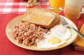 stock photo of hash  - Breakfast of corned beef hash and fried eggs with toast - JPG