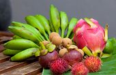 pic of crown green bowls  - Display of tropical fruit on banana leaf on wooden table in natural light - JPG