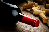 stock photo of flavor  - Bottle of red wine and corks on wooden table - JPG