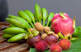 picture of crown green bowls  - Display of tropical fruit on banana leaf on wooden table in natural light - JPG