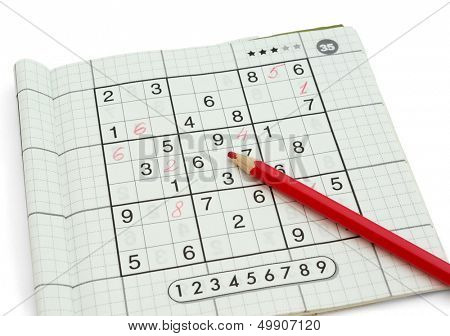 Partially solved Sudoku and red pencil isolated on white