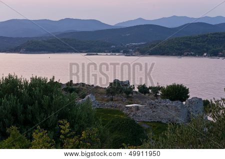 Old roman fortress by the sea at sunset, bay devided with small cape and mountains in background