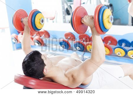 Shirtless young man lifting heavy free weights at the gym