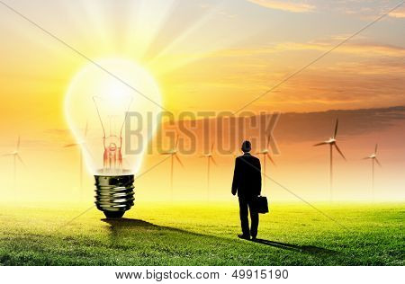 Image of businessman looking at light bulb. Green energy concept