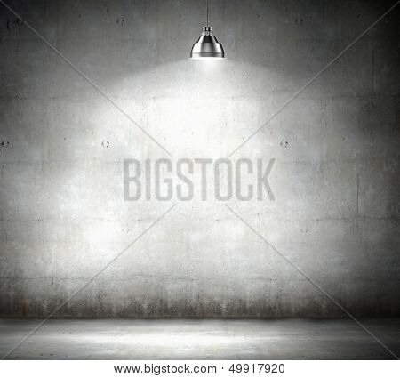Stone blank wall illuminated with hanging above lamp. Place for text