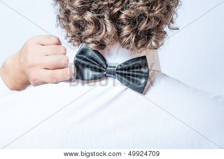 Bow tie on the back side. Strange or fun concept. Back view of an elegant young fashion man in tuxed