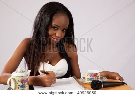 Black woman looking at the camera taking notes