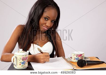 Black woman taking notes with a smile