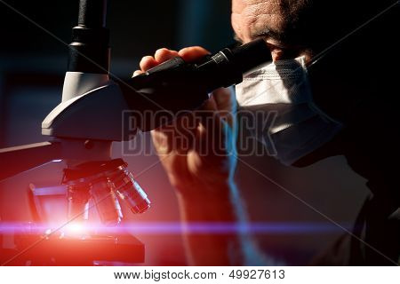 Male scientist watch  in  microscope for  microbiological structures